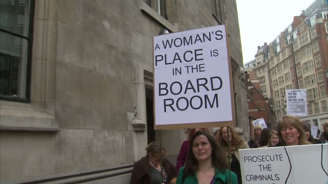 Exterior shots women dressed as Suffragettes walking along street holding placards banners protesting over equality for women Feminists March in...
