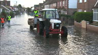 Exterior shots workmen delivering sandbags from back of tractor and trailer to residential houses on flooded street on February 13 2014 in Egham...