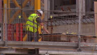 Exterior shots workmen on construction site of luxury apartments wearing hard hats using power tools on July 08 2015 in Liverpool England