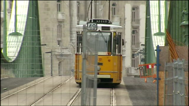 Exterior shots yellow tram street tram Street car travelling through streets and Liberty Bridge on March 08 2009 in Budapest Hungary