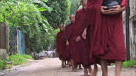 Exterior shots young monks walking through streets in a line and being given rice into bowls by residents Monks Being Given Food In Rangoon Streets...