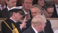 Exterior shotTony Blair sat chatting to man wearing decorated clothing at war memorial service which honoured the service and duty of both the UK...