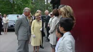 Exterior showing Queen Elizabeth Prince Philip Prince Charles and Camilla meeting and greeting line of officials shaking hands making small...