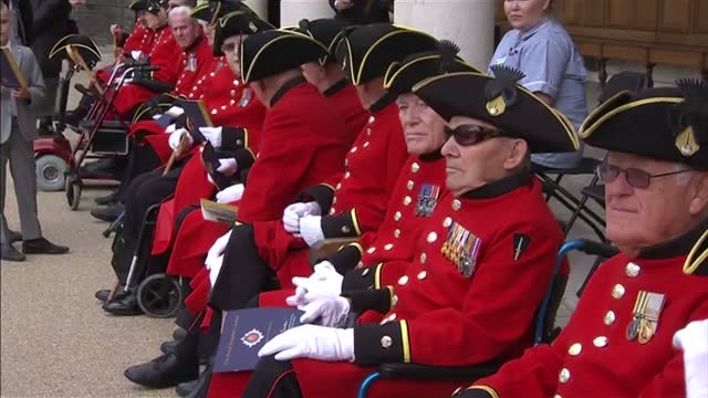 Exterior shows a row of Chelsea pensioners in full military dress seated and waiting for the arrival of Queen Elizabeth