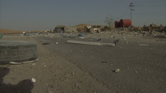 Exterior shows deserted buildings near Mosul debris scattered metal and rubble