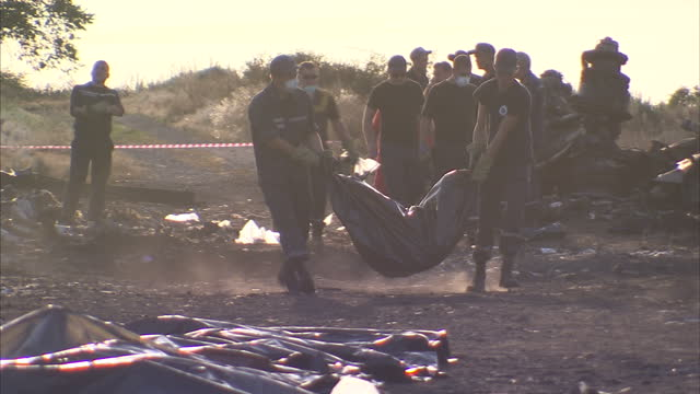Exterior shows rescue workers on or near site of MH17 crash moving body bags of victims on July 22 2014 in Donetsk Ukraine
