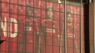 Exterior shows Steven Gerrard and others on promotional material on Kop wall