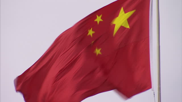 Exterior shows Tiananmen Square with Chinese parliament building Chinese flags flapping in winds