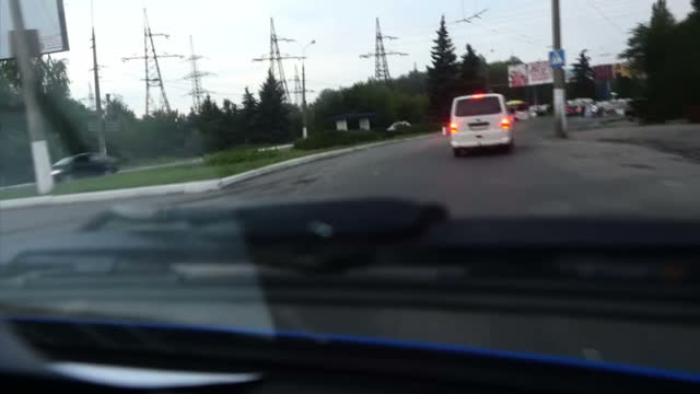 exterior sthot through car windscreen proRussian tanks pass through road / exterior shots through windscreen car drives towards checkpoint / long...