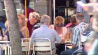 Exterior street scenes tourists enjoying sunny weather in cafe Exterior shots people at Rossio Square relaxing walking around on May 11 2007 in...