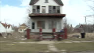 Exterior tracking shot from vehicle along suburban Detroit streets With residential housing large open green spaces abandoned housing and buildings...