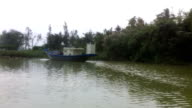 Exterior tracking shots from a boat travelling along the Thu Bon River past a fishing boat and tropical vegetation along the river banks General...
