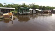 Exterior tracking shots travelling along the Rio Negro near Manaus past a boat hire business and houseboats Manaus market and boats on the Rio Negro...