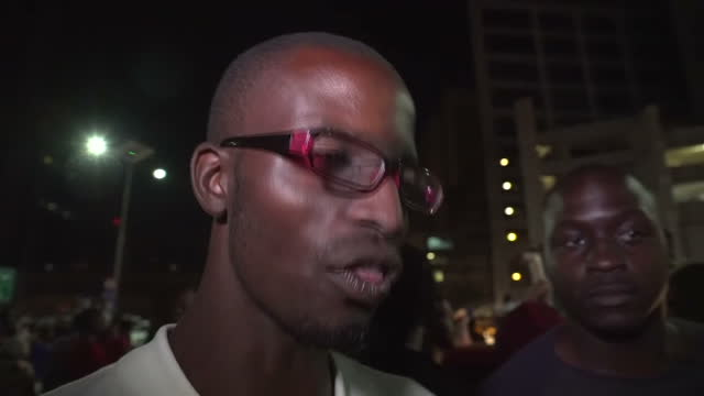 Exterior vox pop interviews with two young men taking part in street celebrations after the announcement of President Mugabe's resignation from...