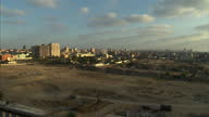 exterior wide shot Gaza City skyline with flashes and smoke from rockets being fired towards Israel