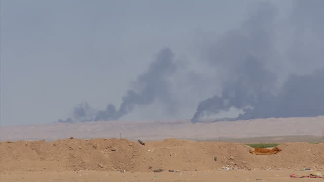 Exterior wide shots of distant palls of black smoke from blazing oil wells set on fire by ISIS militants on March 17 2015 in Tikrit Iraq