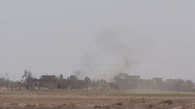 Exterior wide shots of smoke in the distance from ISIS fired artillary explosions on April 20 2015 in Anbar Iraq