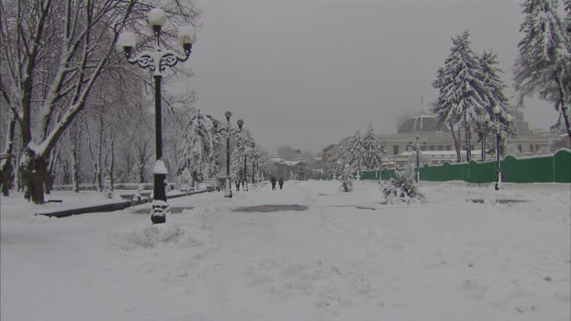 Exterior winter shots of people Ukrainians Kiev residents walking in snow covered park on January 21 2015 in Kiev Ukraine