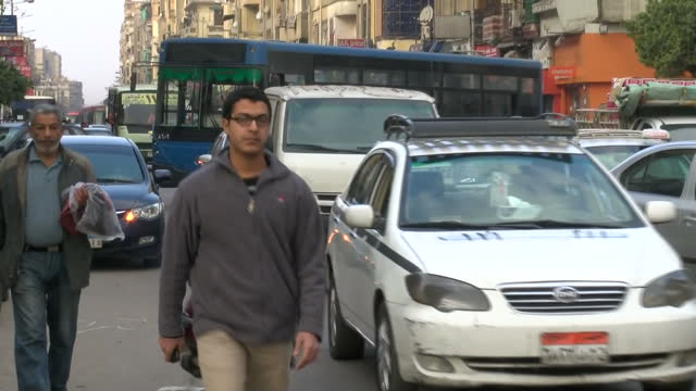 Exteriors showing busy road full of traffic and pedestrians walking alongside on path on February 16 2015 in Cairo Egypt