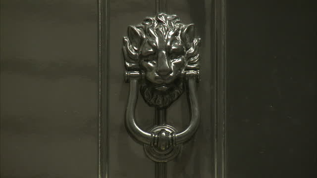 External close shots of the door of Number 10 Downing Street showing the door bell lion's head doorknocker and letterbox with the inscription 'FIRST...