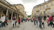 External generic stock shot pan streetscene in Bath town centre various people walking through historic cobbled street all ages some tourists people...