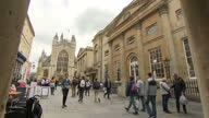 External generic stock shot streetscene in Bath town centre with Bath Abbey Cathedral at end of street various people walking through historic...