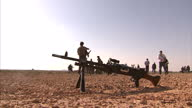 External shots machine gun in desert man on floor in position to shoot Civilians Being Trained With Weaponry on April 27 2011 in UNSPECIFIED Libya