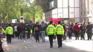 external shots of anticonservative protesters marching towards Downing Street with banners and placards followed by police officers after...