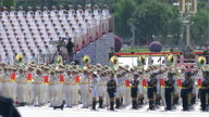 External shots of hundreds of military officials wearing smart white uniform with a yellow belt stood in neat rows stood behind the military parade...