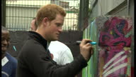 External shots of Prince Harry speaking to volunteers at Russell Youth Club in Nottingham signing his name on a grafitti mural and posing for photo...