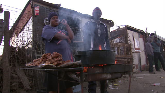 External shots of street vendors cooking meat at a roadside stall in Diepsloot township on the Northern outskirts of Johannesburg Johannesburg...