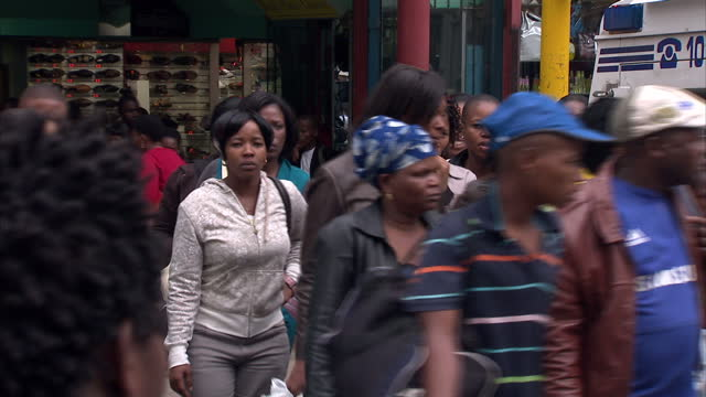 External shots people crossing the street near parked police van which then pulls away Johannesburg Cityscape and Streetscenes on April 15 2013 in...