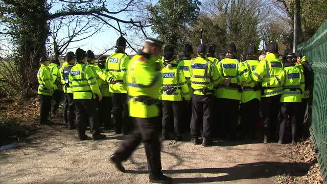 External shots police line pushing back protesters trucks arriving at fracking site on March 11 2014 in Eccles England