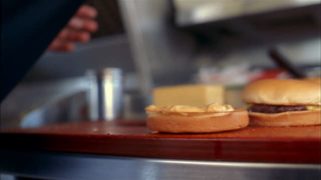 Extreme close up cook placing toppings and bun on cheeseburger on counter in fast food restaurant