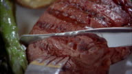 Extreme close up cutting piece of steak w/fork and knife on plate
