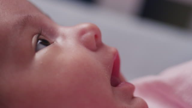 Extreme close up eyes, nose and hungry mouth of a tiny baby as she lays in her crib a yawns.