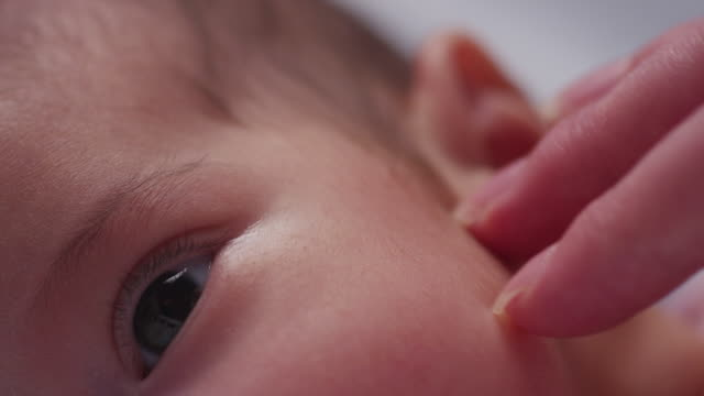 Extreme close up eyes, nose and hungry mouth of a tiny baby as she lays in her crib and mother's fingers touch her forehead.
