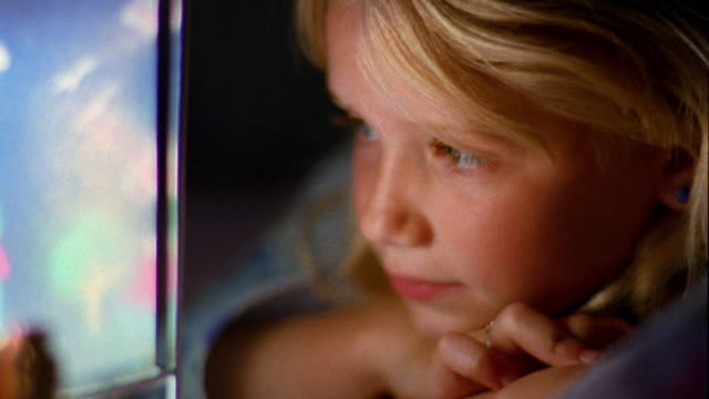 Extreme close up face of young blonde girl resting on arm looking closely at bright carousel lamp