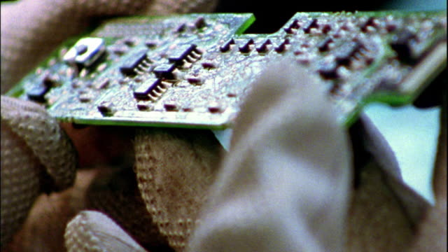 Extreme close up gloved hands examining computer chip board