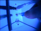 BLUE extreme close up man's fingers attaches cable into telephone/cable TV jack in wall for modem/network hook-up