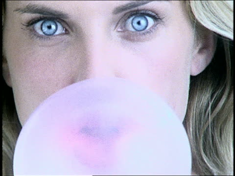 extreme close up of blond woman chewing bubble gum + blowing bubble / bubble bursts on face