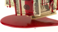 Extreme close up of blood dripping down a group of one hundred dollar bills, creating puddle