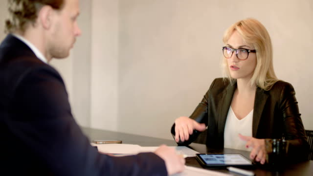 Extreme close up of business woman using tablet computer on a meeting