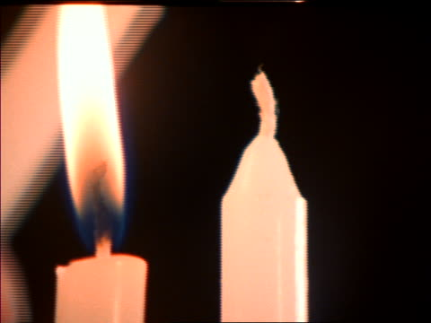extreme close up of candle being lit on menorah