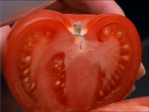 extreme close up of knife slicing tomato