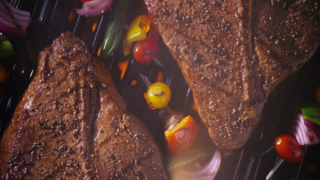 Extreme close up overhead two T-bone steaks & vegetable kabobs grilling - zoom out to wide shot - smoke rises..