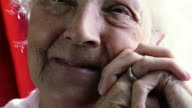 extreme close up PORTRAIT zoom in zoom out senior woman looking into camera / putting hands on face