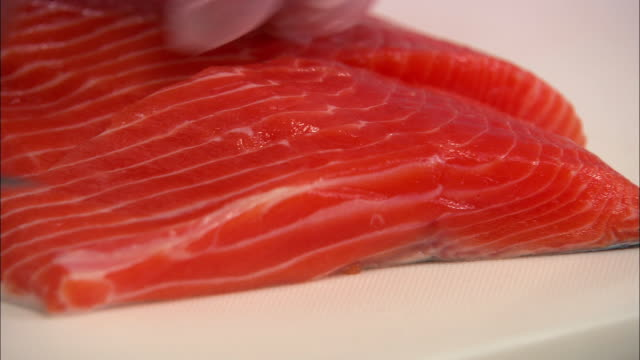 Extreme close up salmon fillet being cut and lifted off cutting board with knife / Auckland, New Zealand