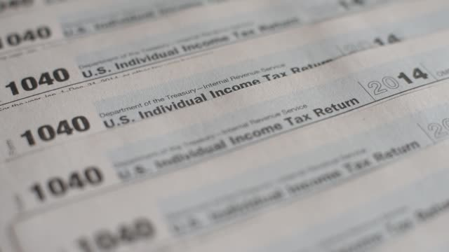 Extreme Close up shots pan across a wooden desktop to reveal a series of 1040 income tax forms arranged for a photo shoot in Tiskilwa Illinois US