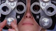 Extreme close up woman having eyes examined / hand turning knobs and adjusting machine
